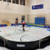 In einer Hallenecke steht ein kleines Floorball Feld. Darin sind mehrere Hüüthen verteilt.